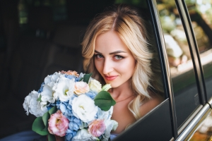 A beautiful bride with curly hair is sitting in the car and looking out the window. Portrait of a bride close-up in a car. Bride with bouquet. Summer wedding.